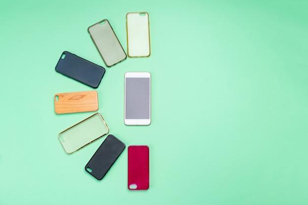 Auswahl an mehrfarbigen kunststoffrückseiten für mobiltelefone auf grünem hintergrund mit einem smartphone an der seite
