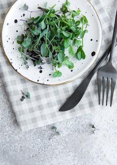 Auswahl an mikrogrüns auf konkretem hintergrund. gesunder lebensstil