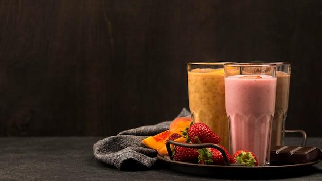 Auswahl an milchshake-gläsern mit früchten und schokolade
