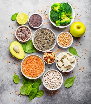 Auswahl an nährstoffreichen lebensmitteln für veganer: bohnen, linsen, quinoa, tofu, gemüse, nüsse, kichererbsen, reis, avocado, obst, rustikaler steinhintergrund, draufsicht. gesunde ausgewogene vegetarische ernährung