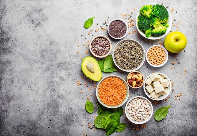 Auswahl an nährstoffreichen lebensmitteln für veganer mit kopierraum: bohnen, linsen, quinoa, tofu, gemüse, nüsse, kichererbsen, reis, avocado, obst, steinhintergrund, draufsicht. gesunde vegetarische ernährung