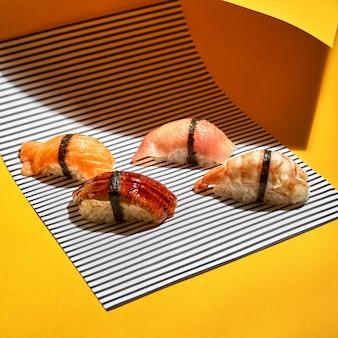Auswahl an nigiri-sushi-mix auf dem leuchtend orangefarbenen hintergrund. frische fischbrötchen für eine gesunde ernährung. selektiver fokus mit kopienraumtext mit harten schatten