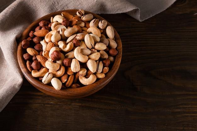 Auswahl an nüssen in holzschale auf dunklem holztisch. cashew, haselnüsse, mandeln und pistazien.