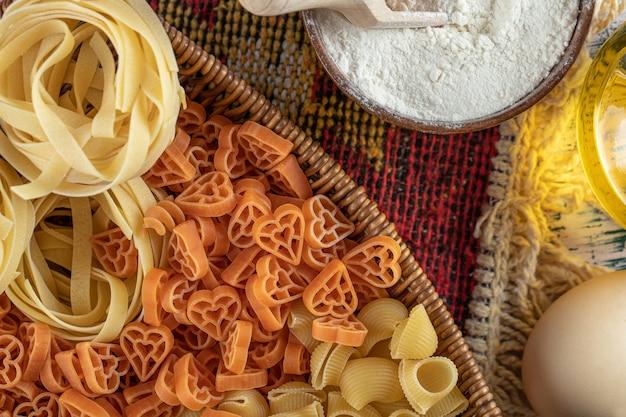Auswahl an rohen nudeln im holzkorb mit mehl und ei.