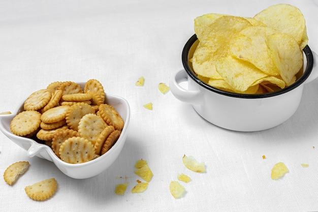 Auswahl an snacks zu hause mit kartoffelchips, bier, crackern, grünen und schwarzen oliven auf dem tisch mit weißer leinentischdecke