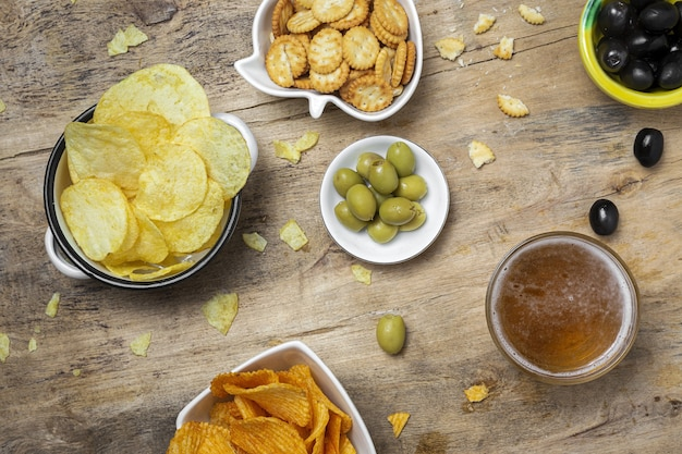 Auswahl an snacks zu hause mit kartoffelchips, bier, crackern, grünen und schwarzen oliven auf holztisch