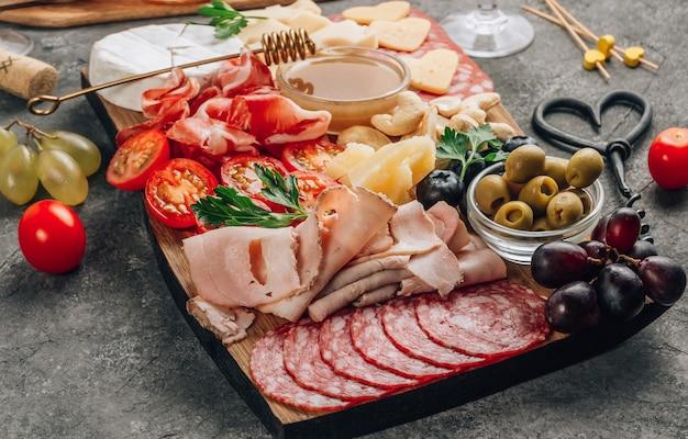 Auswahl an spanischen tapas oder italienischen antipasti mit fleisch, schinken, oliven, käse, nüssen und honig-senf-sauce auf einem konkreten hintergrund. romantisches abendessen mit wein. draufsicht. speicherplatz kopieren
