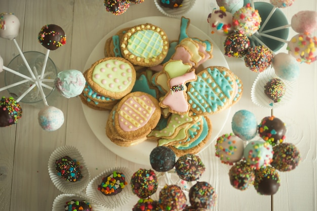 Auswahl an süßigkeiten, cake pops und keksen auf holztisch bei süßwaren