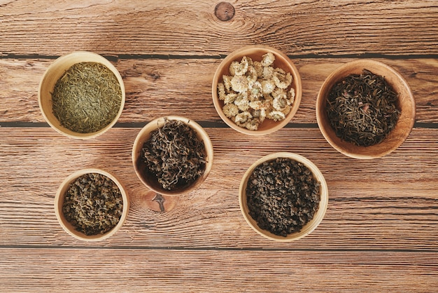 Auswahl an trockenem tee in weißen schalen auf holzoberfläche