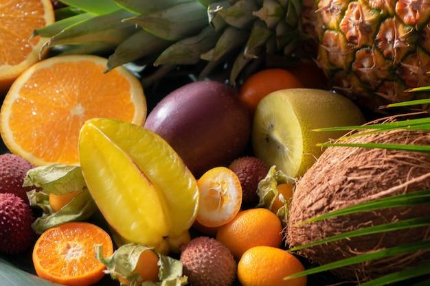 Auswahl an tropischen exotischen früchten: orangenhälften, litschis, karambolen, ananas, zitrone, physalis, kokosnuss, litschi mit palmenblättern aus der nähe