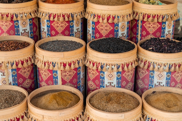 Auswahl an türkischen gewürzen und kräutern in holzschalen. türkische marktgewürze wie safran, sumach und thymian. kreuzkümmel, rosmarin und isot.