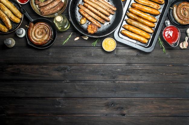 Auswahl an verschiedenen bratwürsten mit saucen. auf einem hölzernen hintergrund.