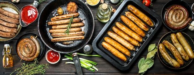 Auswahl an verschiedenen bratwürsten mit saucen. auf einer holzoberfläche.
