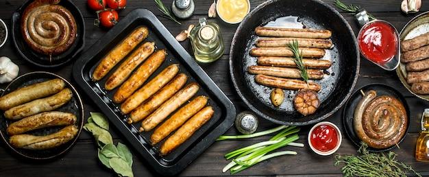 Auswahl an verschiedenen bratwürsten mit saucen auf holztisch.