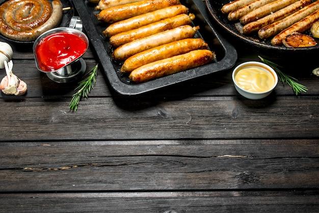 Auswahl an verschiedenen bratwürsten mit saucen auf rustikalem tisch.