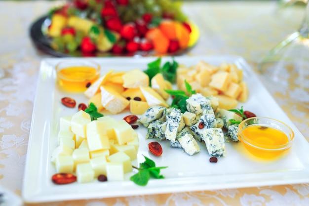 Auswahl an verschiedenen käsesorten mit honig.