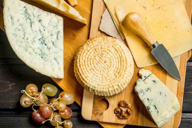 Auswahl an verschiedenen käsesorten mit trauben und walnüssen. auf einem holz.