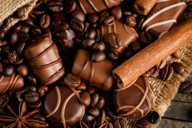 Auswahl an weißer, dunkler und milchschokolade. schokolade mit sahne, nüssen, mandeln, haselnüssen und zimt mit kaffeebohnen. süßes lebensmittel und kein diätkonzept.
