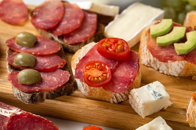Auswahl an wurst und käse, salami camembert brie-scheiben, oliven, auf weißem steinhintergrund. vorspeisentisch mit antipasti-snacks. hintergrund aus weißem marmor. nahansicht