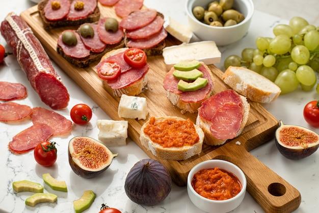 Auswahl an wurst und käse, salami camembert brie, trauben, baguettescheiben, oliven, auf weißem steinhintergrund. vorspeisentisch mit antipasti-snacks. hintergrund aus weißem marmor. nahansicht