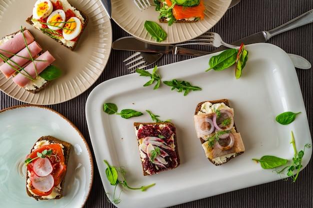 Auswahl dänischer smorrebrod-sandwiches auf teller und teller, besteck auf grauem textiltisch
