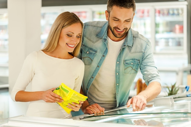Auswahl der produkte für das abendessen. glückliches junges paar, das zusammen produkte auswählt, während es in einem lebensmittelgeschäft in der nähe des kühlschranks steht