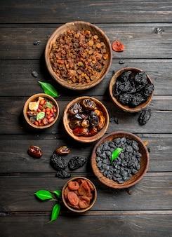 Auswahl verschiedener arten von getrockneten früchten in schalen auf rustikalem tisch.