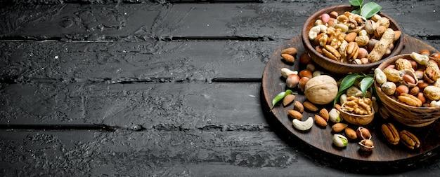 Auswahl verschiedener arten von nüssen in schalen. auf schwarz rustikal.