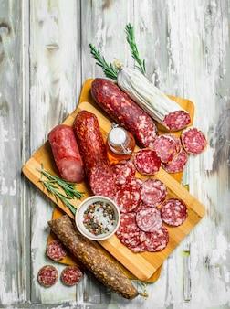 Auswahl verschiedener geräucherter salami auf rustikalem tisch.