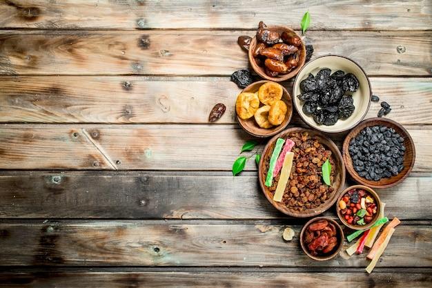 Auswahl verschiedener getrockneter früchte in schalen auf rustikalem tisch.
