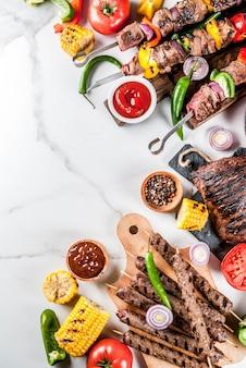 Auswahl verschiedener grillgerichte grillfleisch, grillfest - schaschlik, würstchen, gegrilltes fleischfilet, frisches gemüse, saucen, gewürze,