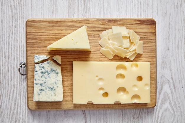 Auswahl verschiedener käsesorten auf holzteller