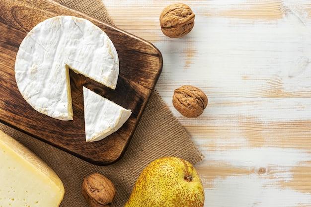 Auswahl verschiedener käsesorten auf weißem holztisch.