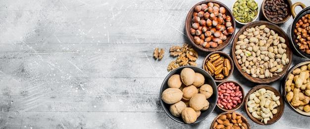 Auswahl verschiedener nüsse in schalen. auf einem rustikalen hintergrund.