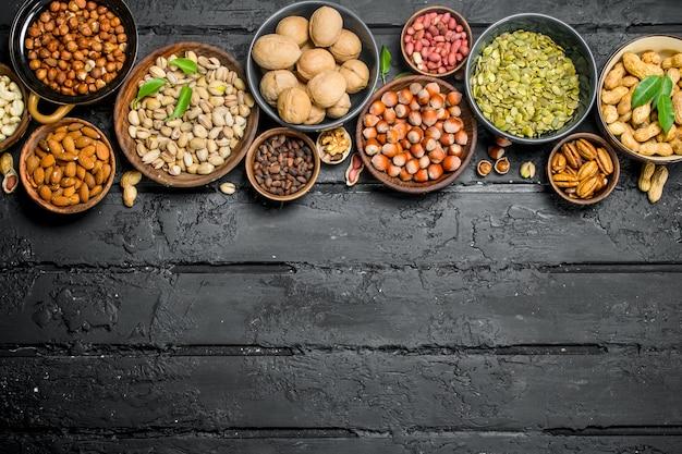 Auswahl verschiedener nüsse in schalen. auf schwarz rustikal.