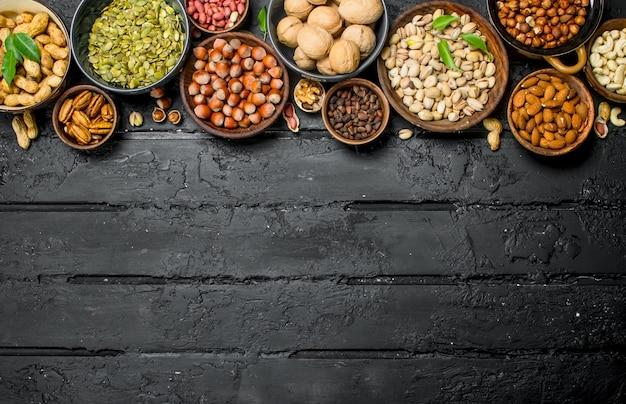 Auswahl verschiedener nüsse in schalen. auf schwarzem rustikalem hintergrund.