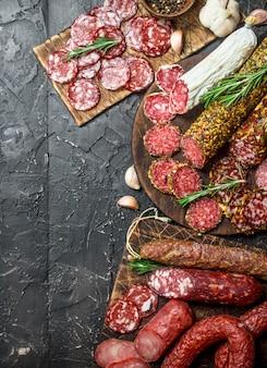 Auswahl verschiedener salami mit gewürzen und kräutern auf schwarzem rustikalem tisch.