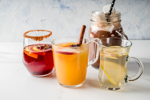 Auswahl verschiedener traditioneller herbstgetränke: heiße schokolade mit marshmallow-tee mit würzigem sangria-glühwein aus zitrone und ingwerweißkürbis