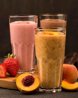 Auswahl von drei milchshake-gläsern mit früchten und schokolade