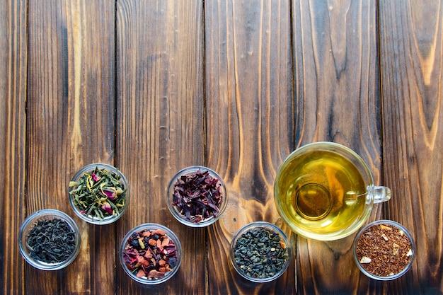 Auswahl von sortierten tees in den transparenten kleinen schüsseln auf natürlichem hölzernem hintergrund