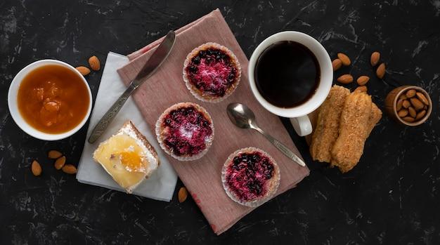 Auswahl von süßen kuchen, von kleinem kuchen und von käsekuchen, heißer kaffee auf dem tisch, mandelnüsse in schüsseln