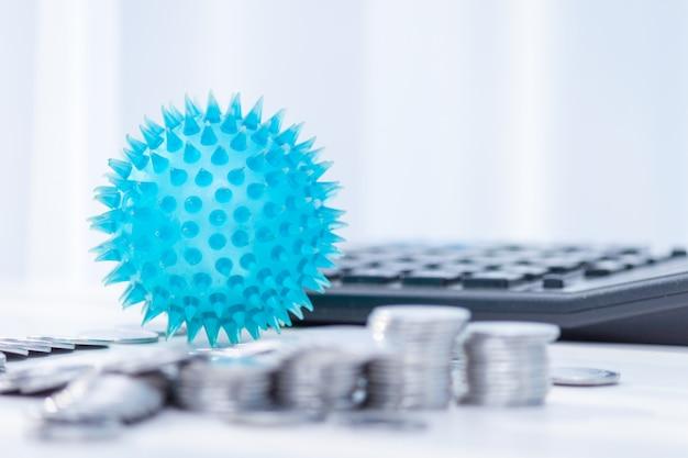 Auswirkungen von coronavirus auf die wirtschaft. münzen, taschenrechner auf dem schreibtisch. medizin- und geldkonzept, ausgaben für covid-19.