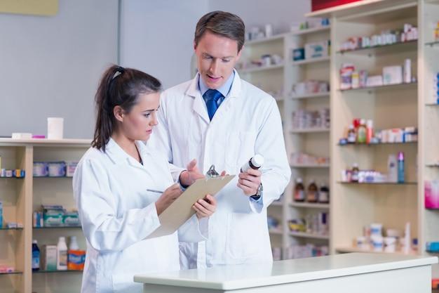 Auszubildender, der eine verordnung beim sprechen mit dem apotheker hält