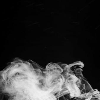 Auszug aus weißen rauchgasen auf schwarzem hintergrund