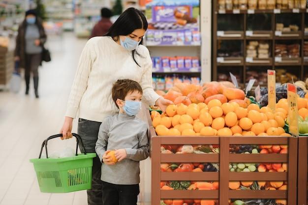 Authentische aufnahme von mutter und sohn, die medizinische masken tragen, um sich vor krankheiten zu schützen, während sie zusammen im supermarkt für lebensmittel einkaufen.