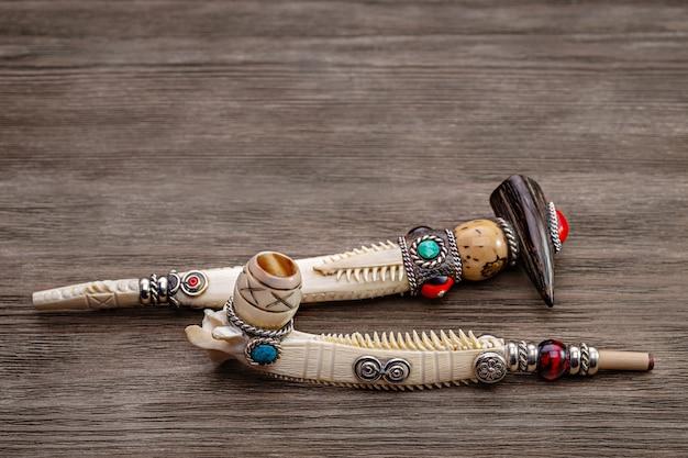 Authentische eingelegte pfeife für tabak aus knochen, auf hölzernem hintergrund. feierliche pfeife der amerikanischen ureinwohner. speicherplatz kopieren.