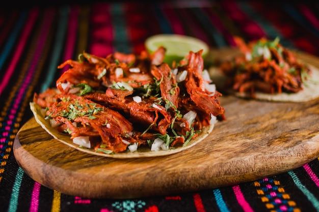 Authentische mexikanische tacos mit mariniertem fleisch, zwiebeln, ananas und koriander, typisch aus mexiko-stadt