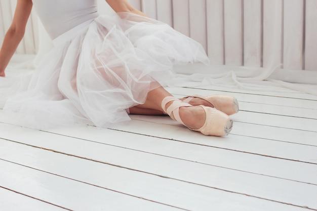 Authentischer ballerina-balletttänzer der jungen frau im pointe shous sitzend auf weißem boden