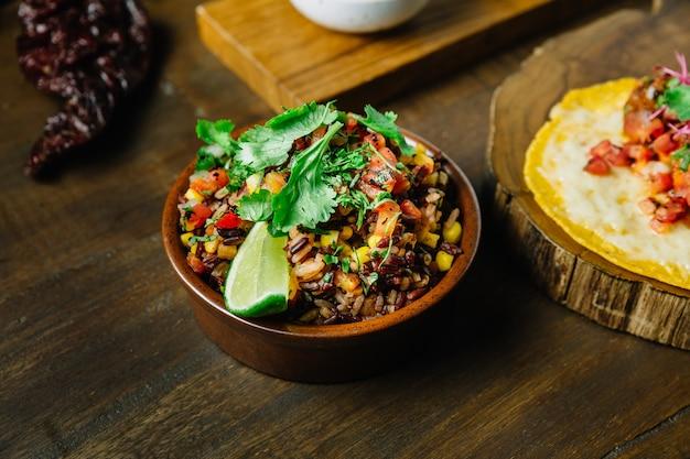 Authentischer mexikanischer reis (arroz rojo) vermischt mit reisbeeren, tomaten und mais.