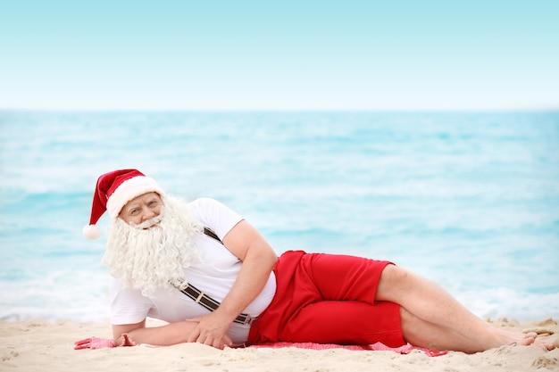 Authentischer weihnachtsmann, der am strand liegt